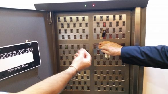 Automotive key management system technology can vary. Image of two hands reaching for keys in a computerized key box.