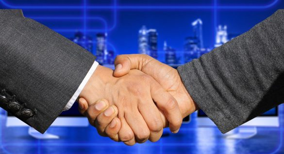 Car Dealership key management - Image of two business men shaking hands in front of a blue cityscape background